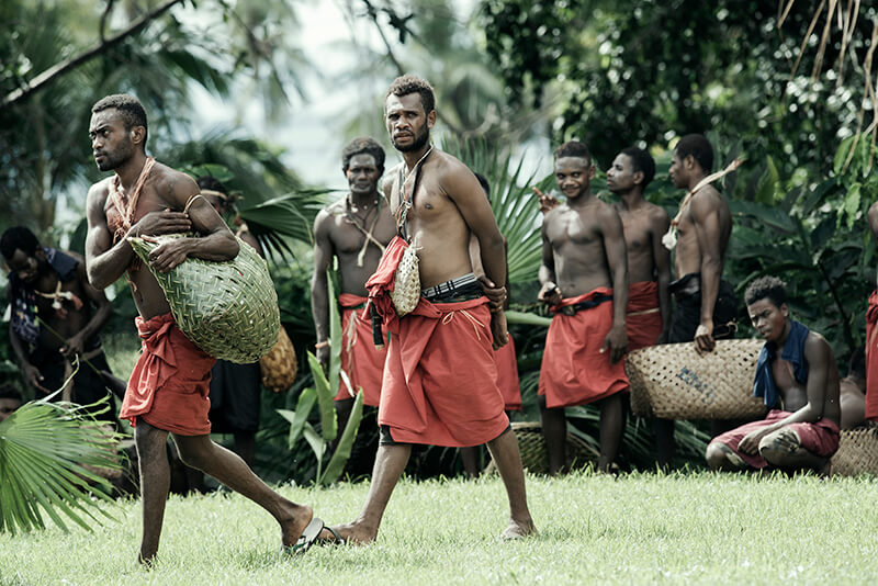 A group of native tribesmen wearing traditional red garments walk across the scene.
