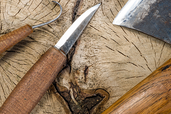 A knife, axe and spoon gouge tools lay upon a wooden tree stump.