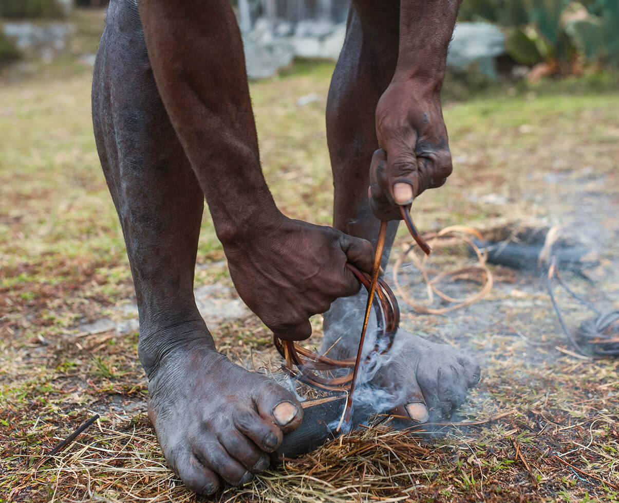 A native tribesman holds a chunk of wood between his feet, and grasps a length of twine in his hands. Rubbing them together, he creates smoke.